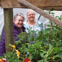 Rosemary Freeman and Elva Sellens enjoy the greenhouse at the Piper Creek Trial Garden